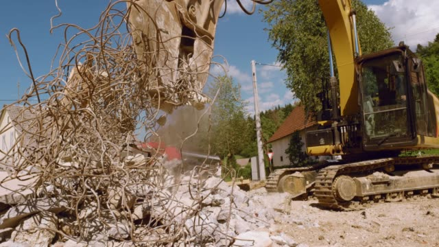 Excavator grapple picking up metal from the pile of construction debris