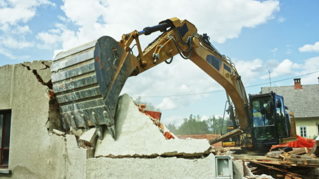 vídeos de stock e filmes b-roll de excavator grapple pushing and pulling the outer walls of an old building to demolish it - escavadora mecânica