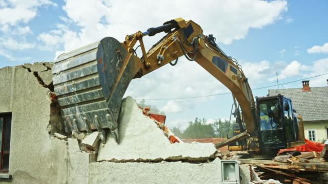 vídeos y material grabado en eventos de stock de grapa de excavadora empujando y tirando las paredes exteriores de un edificio antiguo a demolerla - cavadora mecánica