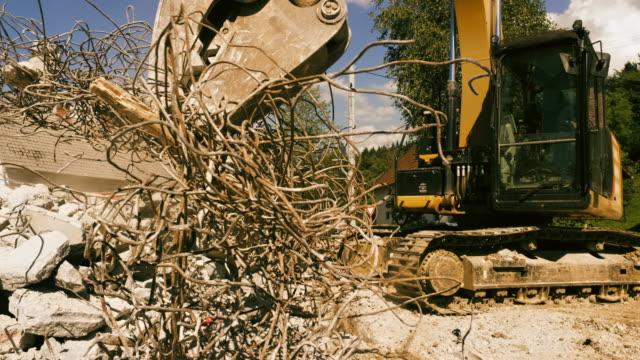 vídeos de stock e filmes b-roll de slo mo excavator grapples clenching metal rods at the construction site - veículo de construção