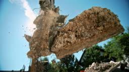 SLO MO Excavator grapples releasing construction debris in sunshine