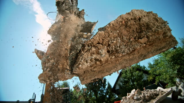 SLO MO Excavator grapples releasing construction debris in sunshine