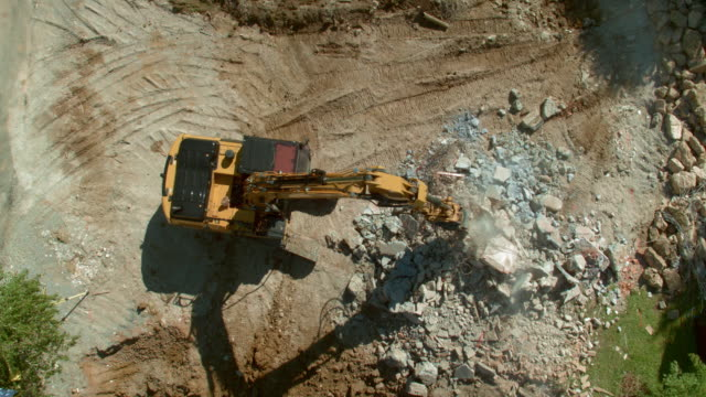 aerial excavator grapples sorting debris at the construction site in sunshine - construction vehicle stock videos and b-roll footage