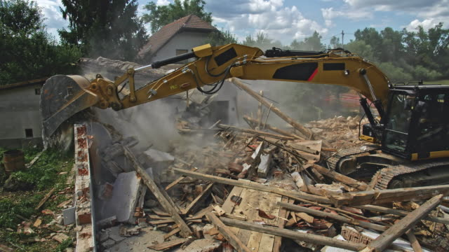 cs excavator in operation at the demolition site taking down the last outer walls of the building - last stock videos & royalty-free footage