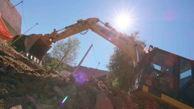 slo mo excavator in operation at the sunny construction site - construction vehicle stock videos and b-roll footage