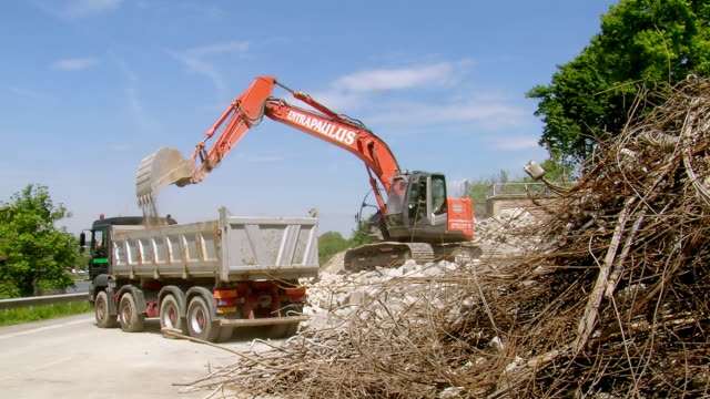 ws excavator loading material in dumper at deconstruction of bridge over river mosel / wellen, rhineland palatinate, germany - dump truck stock videos and b-roll footage