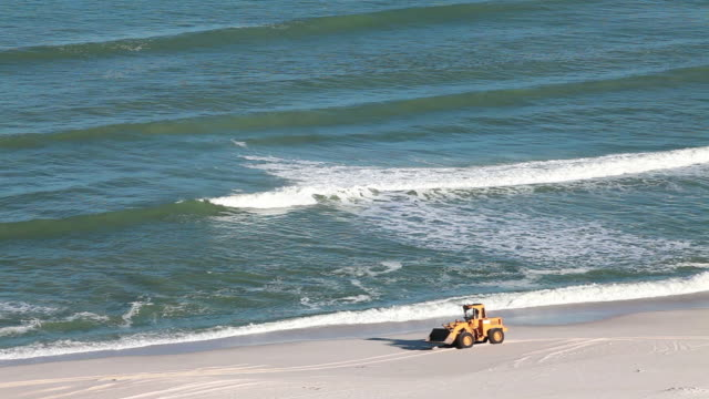 Excavator moves along beach after oil spill