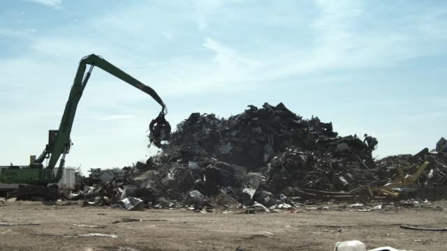WS PAN Excavator moving junk scrap metal to pile, Dallas, Texas, USA