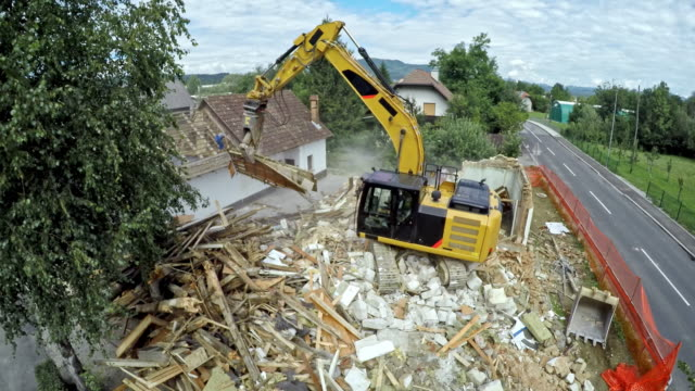ld excavator picking up debris and sorting them at the site of the demolition of an old building - audio available stock videos & royalty-free footage