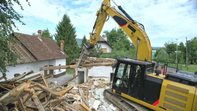 cs excavator picking up the wooden beam off a building being demolished - pala meccanica video stock e b–roll