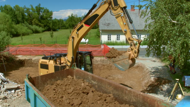aerial excavator placing soil onto the trailer of a truck - construction vehicle stock videos and b-roll footage