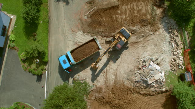 AERIAL Excavator placing the last bucket of soil onto the truck at the building site