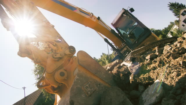 slo mo excavator scraping a layer of soil into the bucket at the construction site - digging stock videos & royalty-free footage