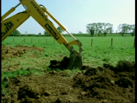 Excavator shovel digging, pan left, England, UK