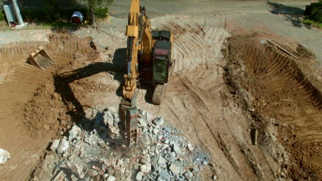 vídeos de stock e filmes b-roll de aerial excavator sorting construction debris at the sunny construction site - veículo de construção