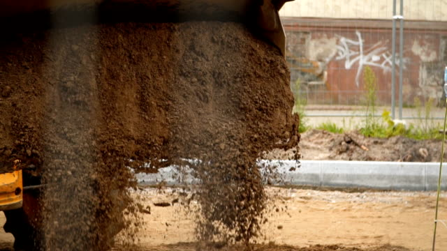 Excavator throws sand slow motion