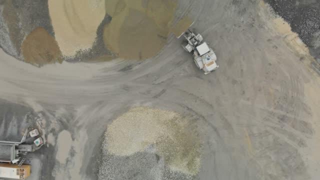 vídeos de stock e filmes b-roll de excavator uldoading gravel on to a pile - working in a quarry - veículo de construção