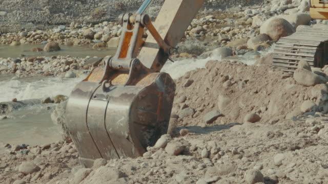 vidéos et rushes de excavatrice travaillant dans une rivière - pelleteuse