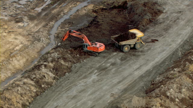 Excavators and dump trucks operate in an oil sands mine in Fort McMurray, Canada.
