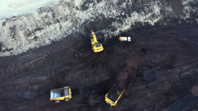 excavators and truck working in coal mine aerial view - minatore video stock e b–roll