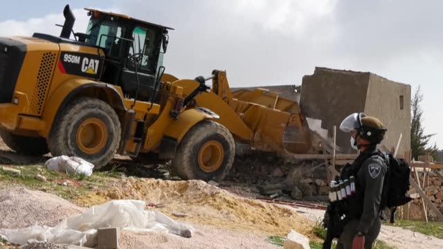 excavators guarded by israeli security forces demolish a palestinian house in a village south of yatta in the southern area of the west bank town of... - hebron west bank stock videos & royalty-free footage