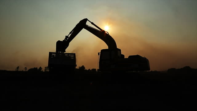 excavators machine  working and silhouette backhoe - roadworks stock videos & royalty-free footage