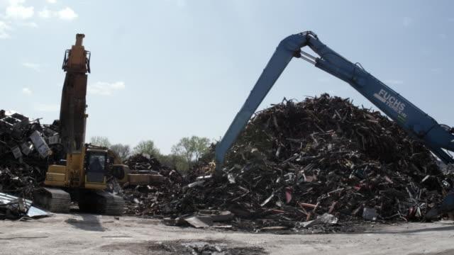 WS Excavators moving junk scrap metal to pile, Dallas, Texas, USA