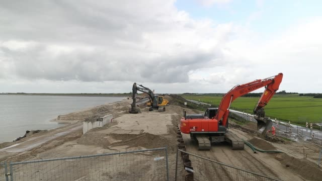 Excavators operate during dike renovation work being carried out by Arcadis NV on the Wadden Sea coastline on Texel island in Oudeschild Netherlands...