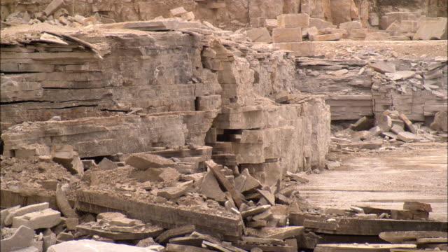 stockvideo's en b-roll-footage met excavators remove sections of limestone in a quarry. - steengroeve