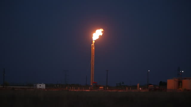 excess gas burning at night in the oil fields surrounding midland, texas, u.s., on thursday, october 15, 2020. - gas stock videos & royalty-free footage