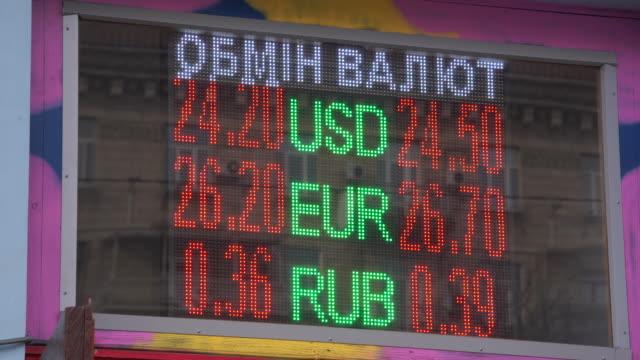 vídeos de stock, filmes e b-roll de exchange rates are seen on an electronic billboard in central kyiv, ukraine on february 20, 2020. - casa de câmbio