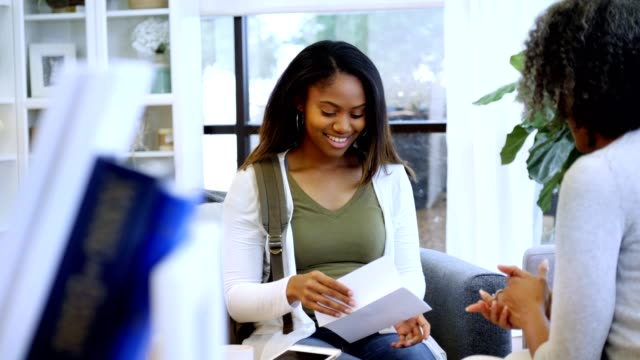 excited african american teenage girl receives college acceptance letter - letter document stock videos & royalty-free footage