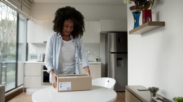 興奮したアフリカ系アメリカ人女性は、それを振って微笑む自宅でパッケージを受け取る - 段ボール箱点の映像素材/bロール