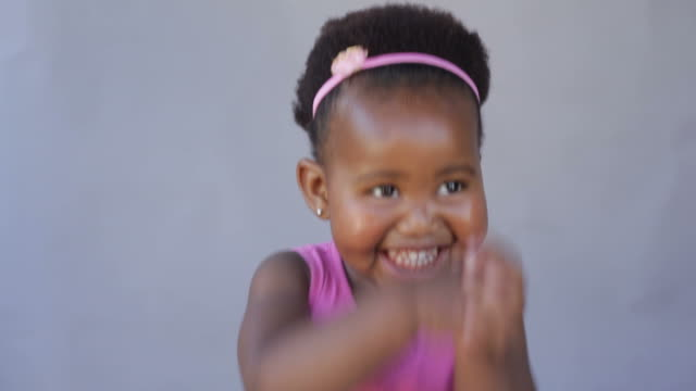 Excited african baby girl dancing with joy