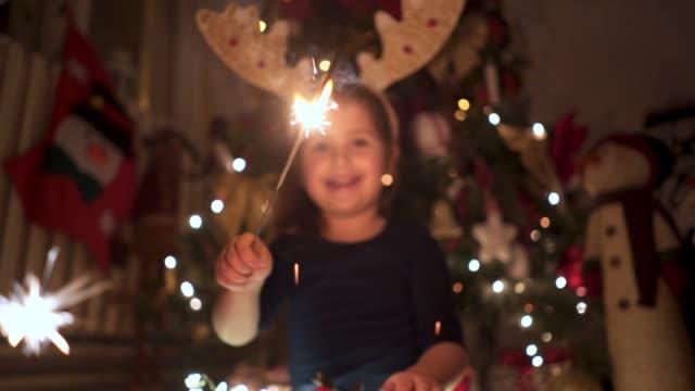 stockvideo's en b-roll-footage met enthousiast en vrolijke peuter spelen met schittert tijdens een new year's eve - nieuwjaar