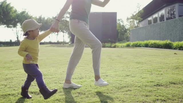 upphetsad asiatiska pojke kör med hans mor i parken - pojkbaby bildbanksvideor och videomaterial från bakom kulisserna