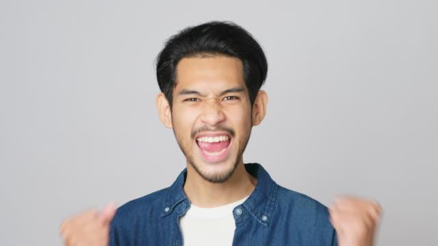 vidéos et rushes de homme asiatique excité célébrant le succès tout en se tenant au-dessus du fond gris clair, heureux asiatique mâle gagnant, atteignant la réalisation, le geste positif de headshot et l'expression faciale, résolution de 4k - atteindre