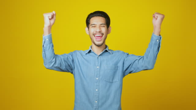 vídeos de stock e filmes b-roll de excited asian man celebrating success while standing over yellow background, happy asia male wining, reaching achievement, positive gesture and facial expression, portrait, 4k resolution - mão levantada