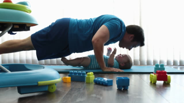 excited baby watching dad do press ups - multitasking stock-videos und b-roll-filmmaterial
