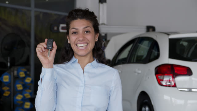 vídeos de stock e filmes b-roll de excited beautiful young woman holding the keys to her new car smiling at camera - aluguer de automóveis