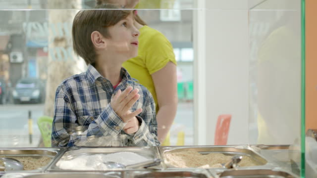 excited boy and girl waiting at the glass counter of cake shop - performing arts event stock videos & royalty-free footage