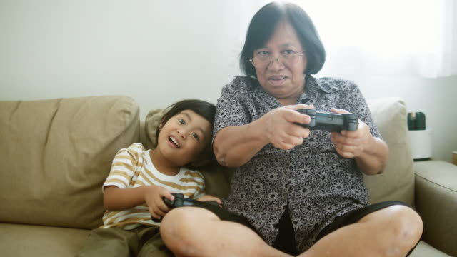 excited boy competing in video game with grandmother at home - gamepad stock videos & royalty-free footage