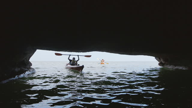 Excited boy in kayak pumps paddle in the air outside sea cave on family vacation.