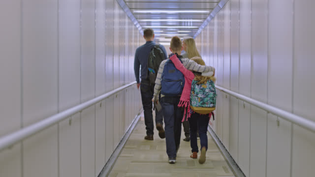 excited boy puts arm around young sister as family of four walks down jet bridge. - gate stock videos & royalty-free footage