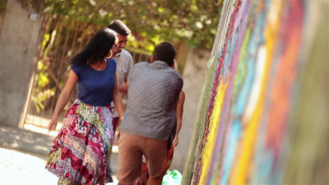 excited brazilian friends walk and talk along graffitied wall in rio de janeiro - gesturing stock videos & royalty-free footage