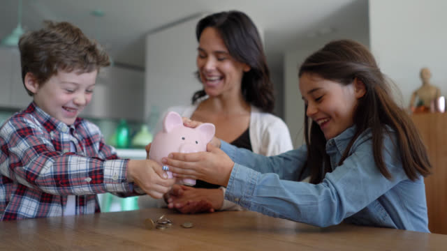 excited brother and sister opening their piggybank together while mom is sitting between them very happy and smiling - family with two children stock videos & royalty-free footage