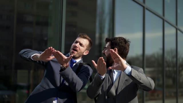 vidéos et rushes de partenaires d'affaires excités dansant à l'extérieur - collègue