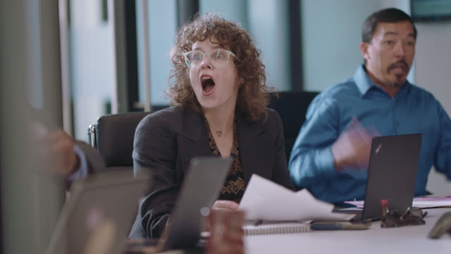 vidéos et rushes de excited business professionals celebrate with dancing, screaming, and high fiving together in a office board room - collègue