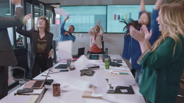 excited business professionals erupt with cheers and high fives as they celebrate good news in a corporate board room - winning stock videos & royalty-free footage
