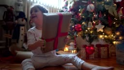 Excited child shaking presents before opening them on Christmas morning